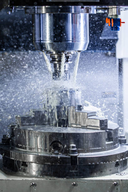 Vertical photo of industrial wet milling process in 5-axis cnc machine with coolant flow under pressure and freezed splashes stock photo
