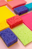 Vertical photo of polyurethane dish sponges and other cleaning stuff isolated on pastel pink background