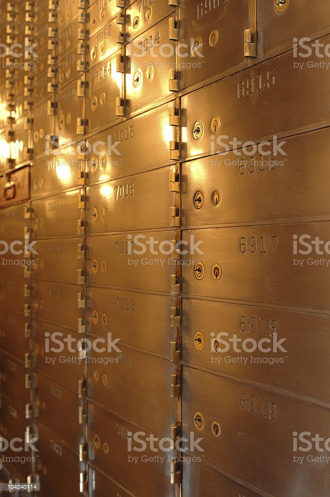 Vertical photo of safety deposit boxes in yellow light stock photo
