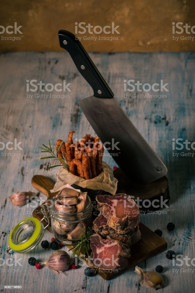Vertical photo of stacked pieces of dried smoked meat from italian wild boar. Meat is on vintage chopping board and blue wooden table with sausages, garlic, black thorns and big cleaver. stock photo