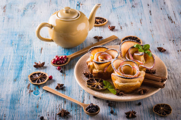 Vertical photo with crispy dessert. Sweet is made from apple slices and puff pastry. Dessert is called apple roses. Several herbs and spices are spilled around with powder sugar. stock photo