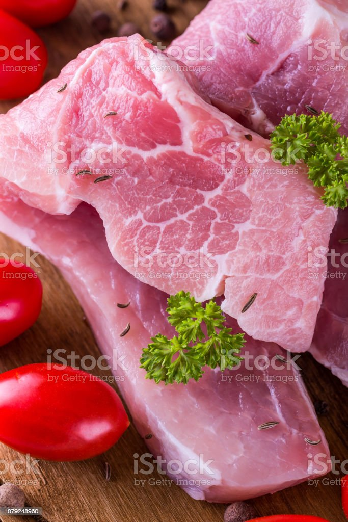 Vertical photo with few long and thin slices of pork meat with fat on the edge. The green parsley twigs and single rosemary with tomatoes are next to meat. Raw food is on wooden chopping board. stock photo