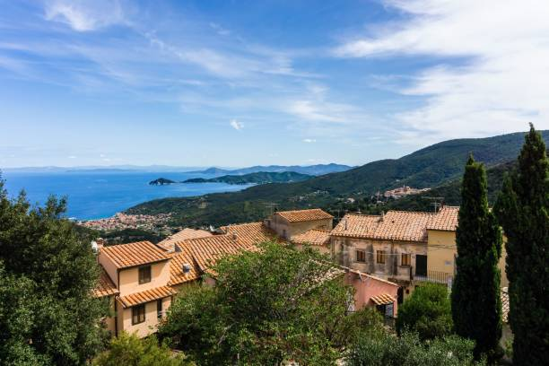 Vertical photo with view on the bay of town Marciana Marina on the coast of Elba island. The view is over few houses of small historical village Marciana Alta. Sky is blue with several clouds. stock photo