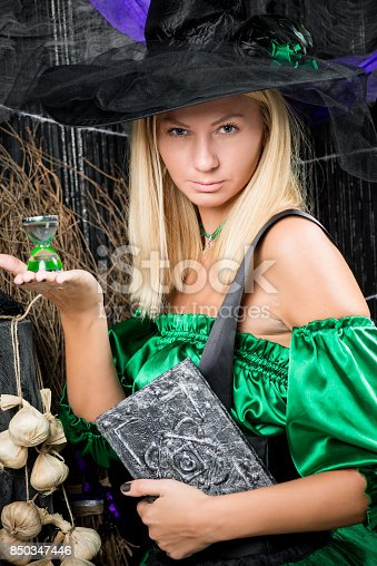 istock vertical portrait of a beautiful witch with a magic book in his hands 850347446