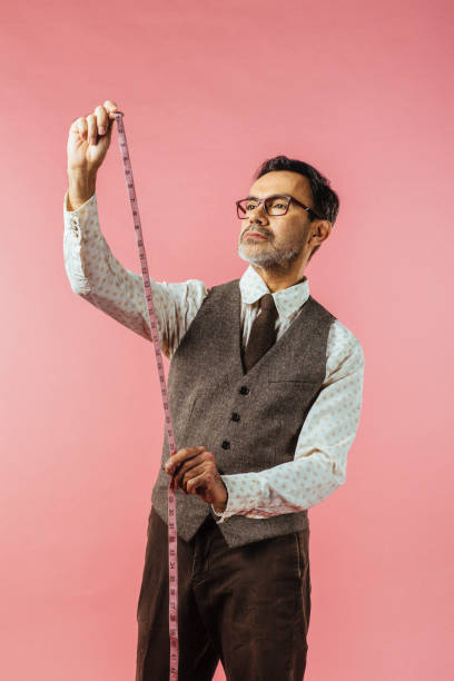 vertical portrait of a tailor holding fabric measure, isolated on pink studio background - carlos david stock pictures, royalty-free photos & images