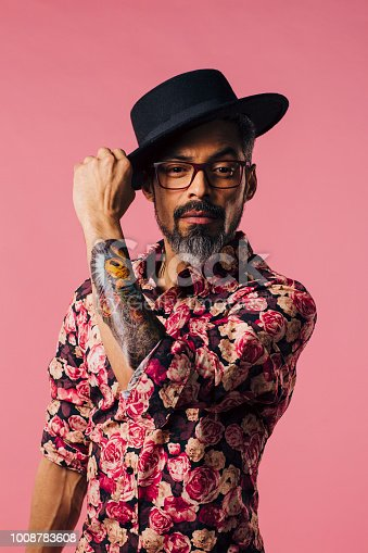 Vertical portrait of a very cool man with tattoos, tilting his hat, isolated on pink studio background