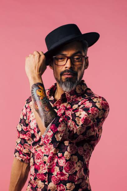 vertikale porträt eines sehr cool mit tattoos, seinen hut zu kippen - alte tattoos stock-fotos und bilder