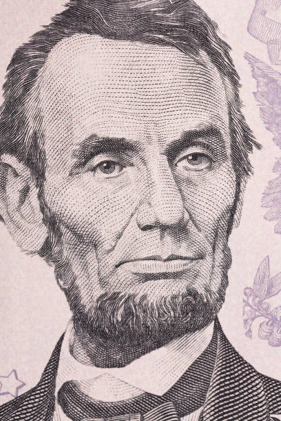 Vertical portrait of Abraham Lincoln's face on the US 5 dollar bill. Macro shot stock photo