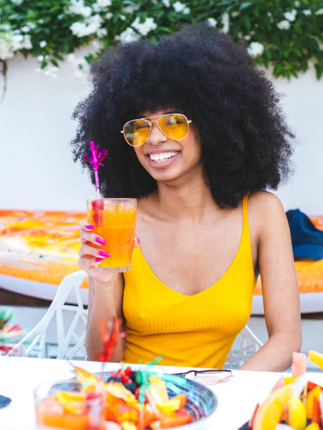 Vertical portrait of beautiful African-American smiling girl with afro hairstyle drinking cocktail and eating fruit, vertical image