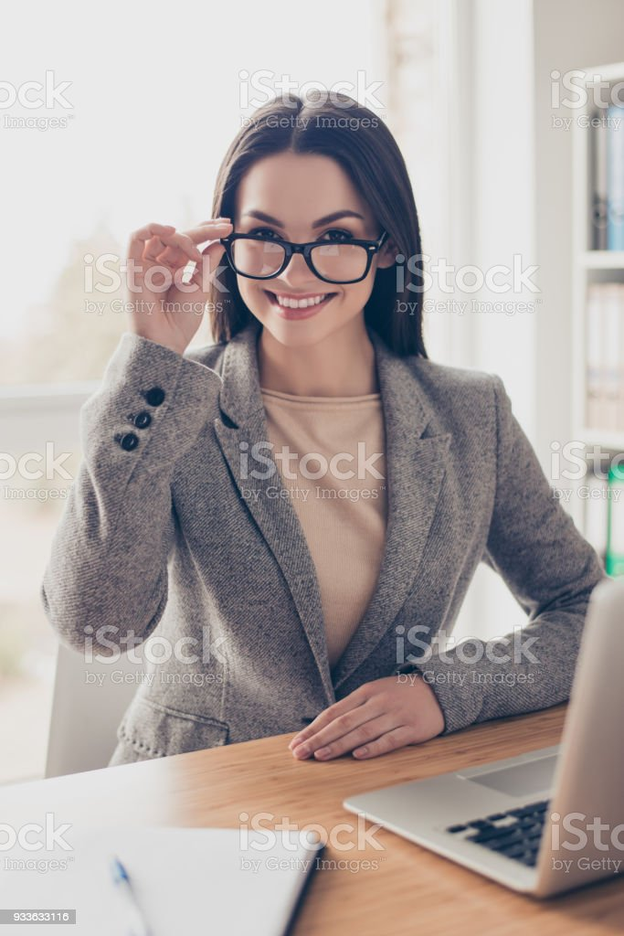 Vertical portrait of beautiful experienced qualified pretty cheerful joyful woman wearing grey jacket sitting at the table touching glasses at modern light office stock photo