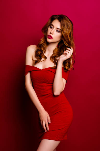 vertical retrato de mujer de ensueño, apuesta, seductor, magnífico, exquisita en mini vestido, peinado rizado moderno aislado sobre fondo rojo intenso soporte media vuelta - buenos culos fotografías e imágenes de stock