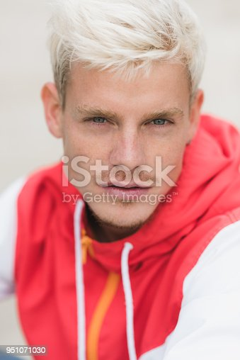 istock Vertical portrait of fashion style portrait of handsome attractive blond man with serious look posing against white wall outside. Male model looking at the camera. People, lifestyle concept. 951071030