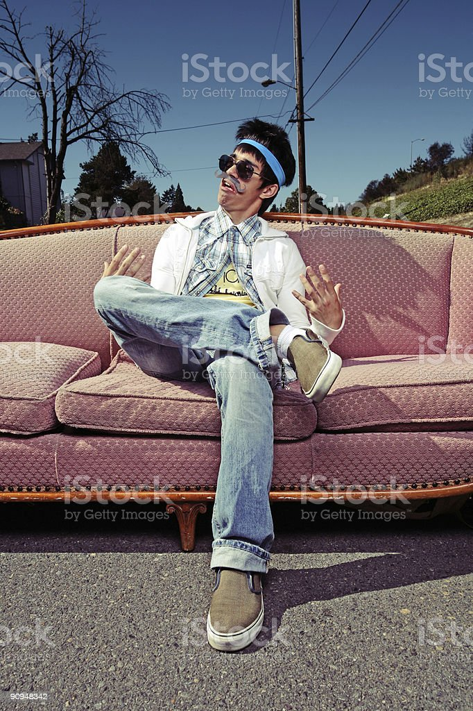 Vertical Portrait of Humorous Sitting Male on Outdoors Vintage Couch royalty-free stock photo