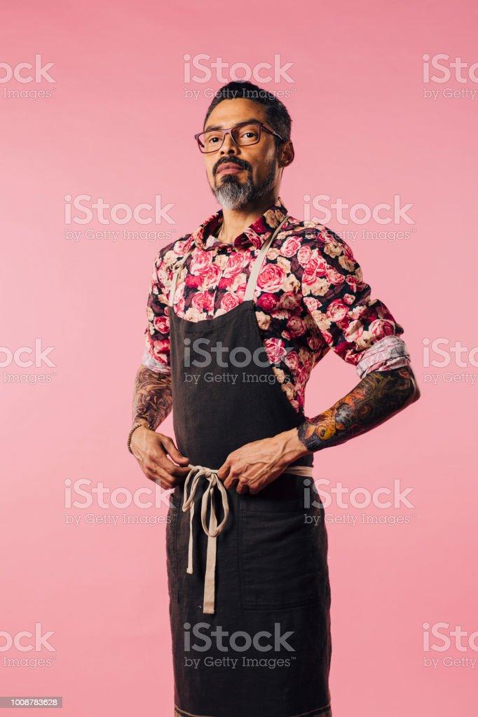 Retrato vertical do chef orgulhoso, com tatuagens e mãos na cintura - foto de acervo