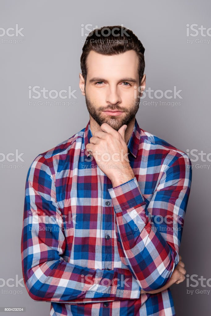 A vertical portrait of stylish bearded handsome guy touching his chin and posing against gray background stock photo