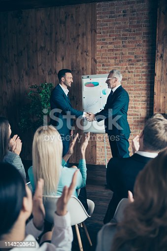 924520144 istock photo Vertical profile side view of nice stylish elegant professional managers wearing suits shaking hands welcome to new start-up finance project at industrial loft interior work place space indoors 1143203643