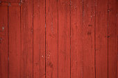 Vertical oxblood red barn door boards and planks background. One red hinge.