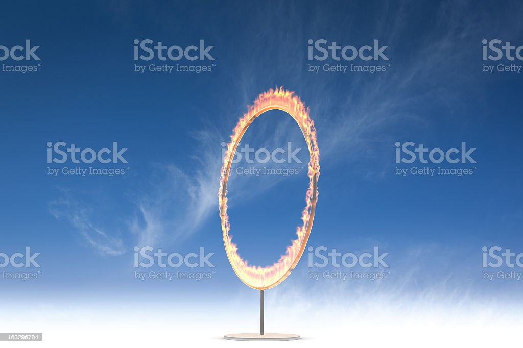 A vertical ring of fire on a stand in front of a blue sky royalty-free stock photo