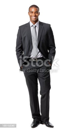 Portrait of a handsome young businessman standing with his hands in his pockets. Vertical shot. Isolated on white.