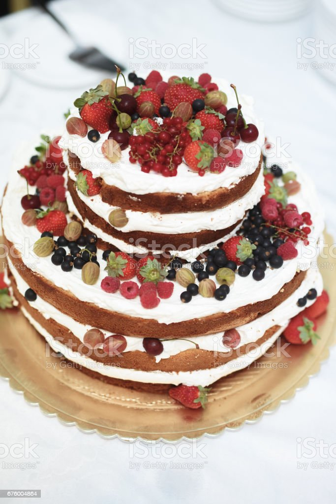 Vertical Shot Of A Rustic Style Wedding Cake With Fresh Berries