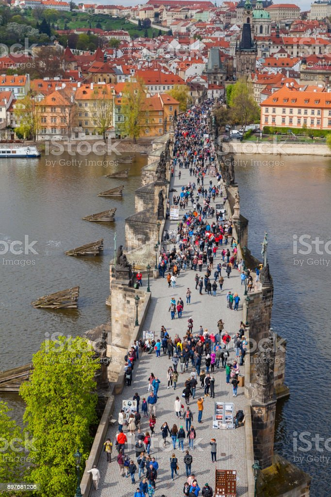PRAGUE, CZECH REPUBLIC - APRIL 23, 2016: Vertical shot of Charles bridge over Vltava river with walking tourists stock photo