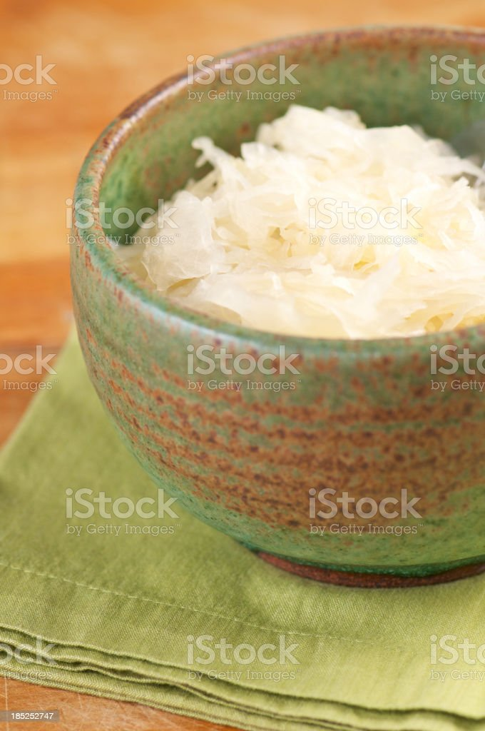 Vertical Shot of Sauerkraut in Green Pottery Bowl royalty-free stock photo