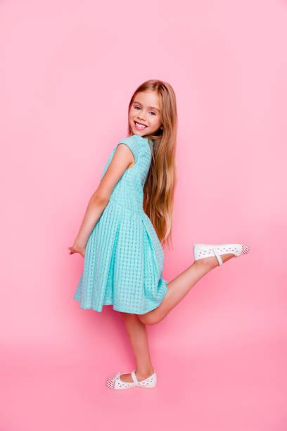 vertikale seite ansicht in voller größe, full-length porträt des niedliche schöne sanfte zarte kleine mädchen leichten blauen kleid, sie lächelt und hob ein bein, auf rosa hintergrund isoliert - prinzessinnenschuhe stock-fotos und bilder