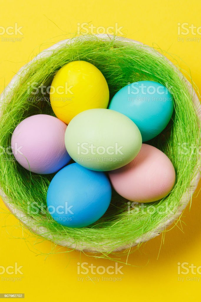 Vertical six colorful pastel painted Easter eggs in basket with green grass isolated on yellow background. Happy Easter concept. Copy space for advertisement. With place for text. Top view on eggs. stock photo