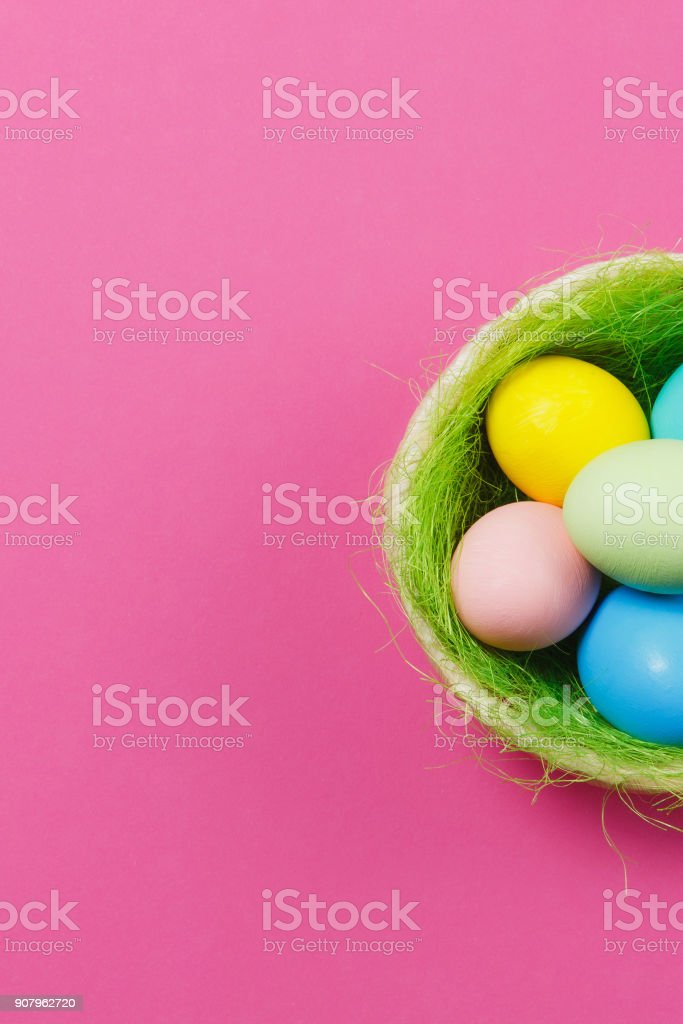 Vertical six colorful pastel painted Easter eggs in basket with green grass isolated on pink background. Happy Easter concept. Copy space for advertisement. With place for text. Top view on eggs. stock photo