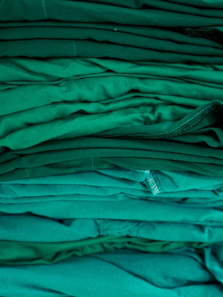 Vertical stack of green surgical gowns stock photo