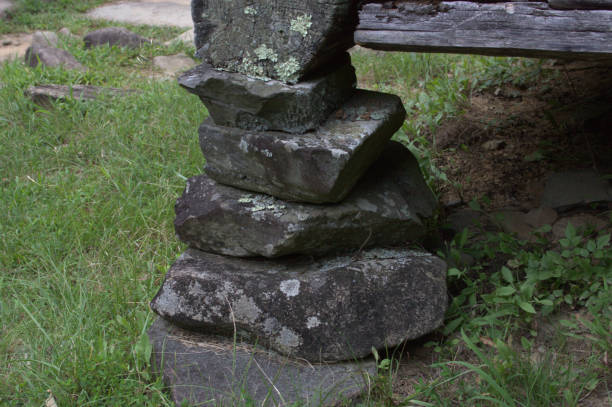 Vertical stack of rocks holding up the corner of a building stock photo