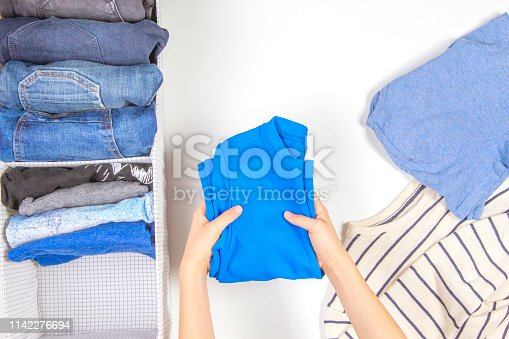 1146468292 istock photo Vertical storage of clothing, tidying up, room cleaning concept. Hands tidying up and sorting kids clothes in basket. 1142276694