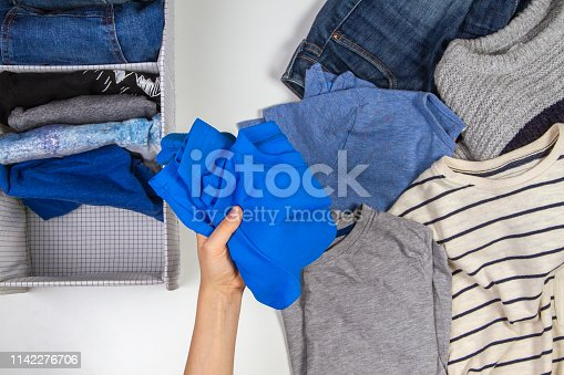 1146468292 istock photo Vertical storage of clothing, tidying up, room cleaning concept. Hands tidying up and sorting kids clothes in basket. 1142276706