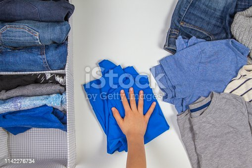 1146468292 istock photo Vertical storage of clothing, tidying up, room cleaning concept. Hands tidying up and sorting kids clothes in basket. 1142276734