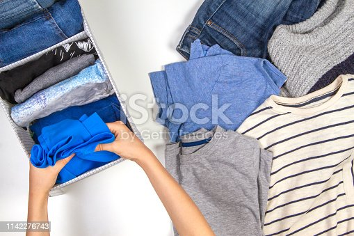 1146468292 istock photo Vertical storage of clothing, tidying up, room cleaning concept. Hands tidying up and sorting kids clothes in basket. 1142276743