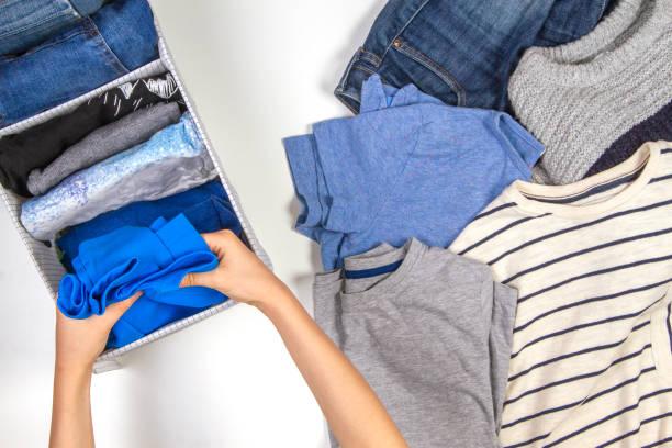 pionowe przechowywanie odzieży, sprzątanie, koncepcja sprzątania pokoju. ręce porządkowanie i sortowanie dzieci ubrania w koszu. - odzież zdjęcia i obrazy z banku zdjęć