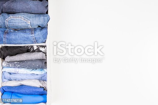 istock Vertical storage of clothing, tidying up, room cleaning concept. Stack of folded clothes in basket with heap unholded clothes on white background 1142276719