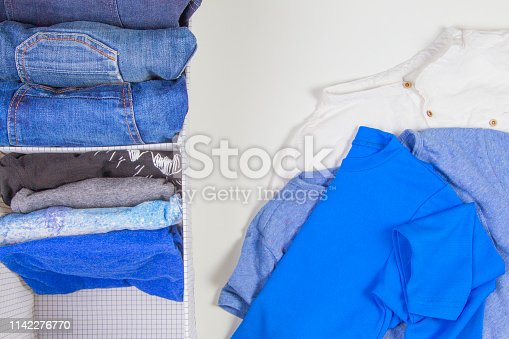 istock Vertical storage of clothing, tidying up, room cleaning concept. Stack of folded clothes in basket with heap unholded clothes on white background 1142276770