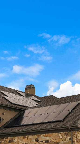 Vertical tall frame Cloudy blue sky over a home with solar panels on the pitched roof stock photo