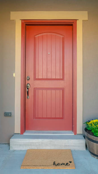 Vertical The red front door of a house with concrete exterior wall and shutters on window stock photo