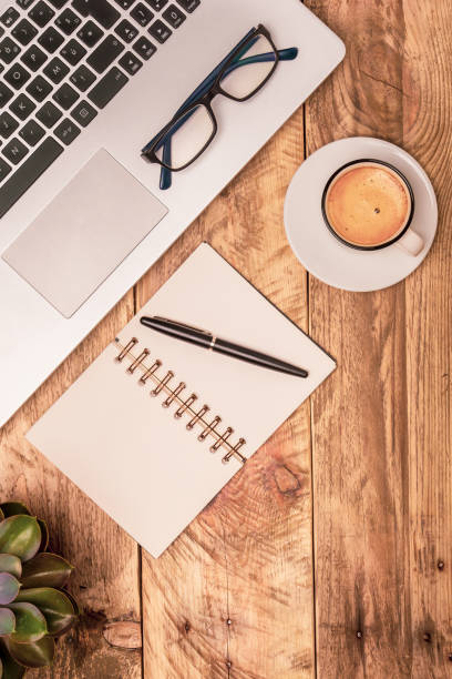 Vertical top view composition of modern office workspace with laptop, note book, coffee and plant on a rustic wooden desk. Office work, study, writing concepts. stock photo