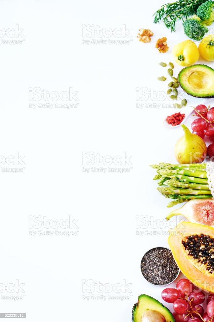 Vertikale Draufsicht von frischem Obst und Gemüse, Nüssen, Samen, Superfoods auf einem weißen Hintergrund mit einem Leerzeichen kopieren. – Foto