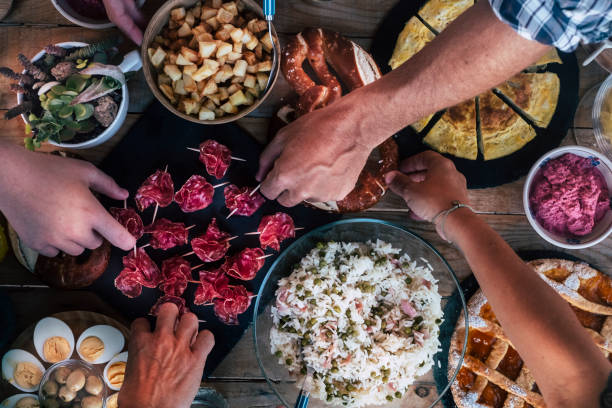 Vertical top view of friends eating together  on a wooden table full of food - friendship and celenration people - concept of friendship with adult men and women at home or restaurant stock photo