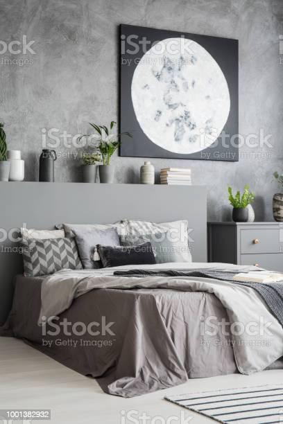 Vertikale Ansicht Von Einem Modernen Schlafzimmer Innenraum In Grauer Farbe Mit Einem Grossen Bett Mit Kissen Und Bettwasche In Der Front Und Ein Mondgemalde An Der Wand Echtes Foto Stockfoto Und Mehr