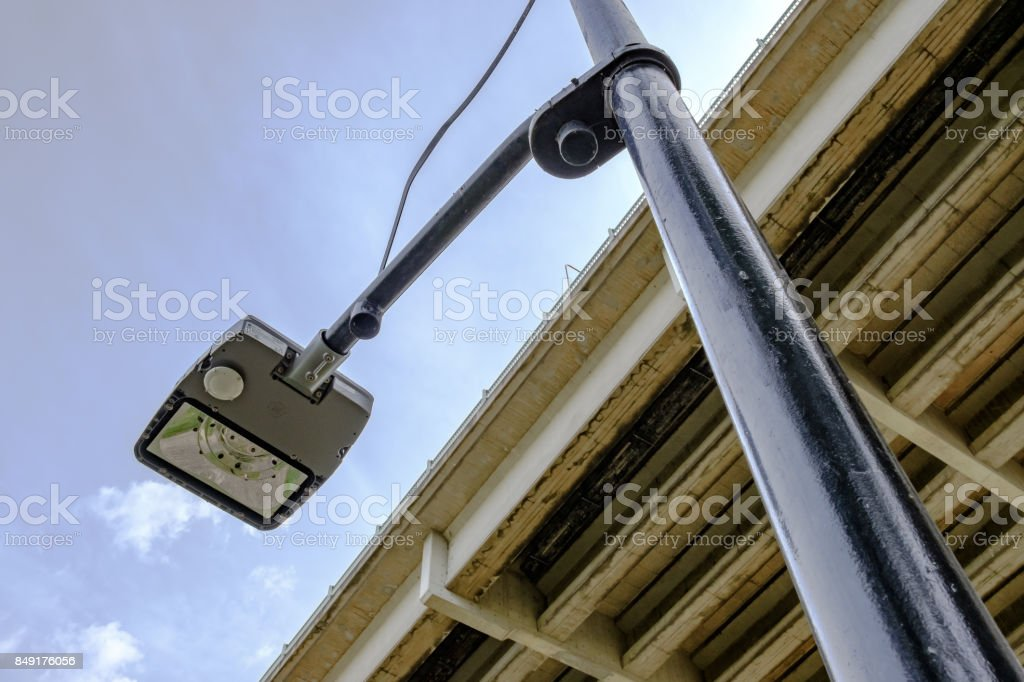 Vertical view of a new, low energy LED street light seen in front of a motorway bridge. stock photo
