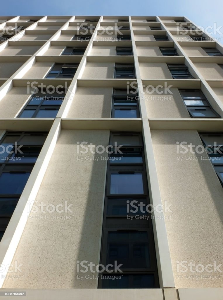 vertical view of a tall concrete angular modern high building with geometric white details against a blue sky stock photo