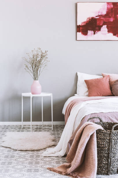 Vertical view of pink and grey bedroom interior with wicker basket and flowers in vase stock photo