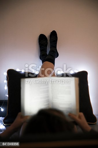 501914364istockphoto Vertical view of Woman lying in bed while reading book 641349356