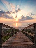 A vertical sunrise viewpoint down the pedestrian walkway to the beach.