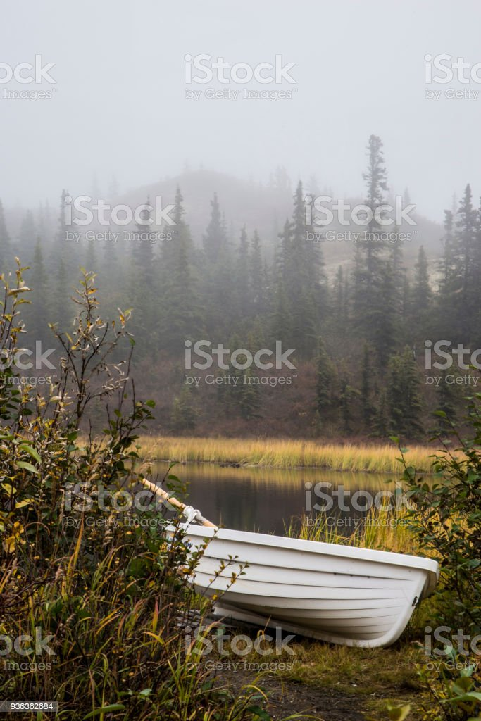 Vertical-a small row boat sits among the fog along the side of a kettle pond. stock photo